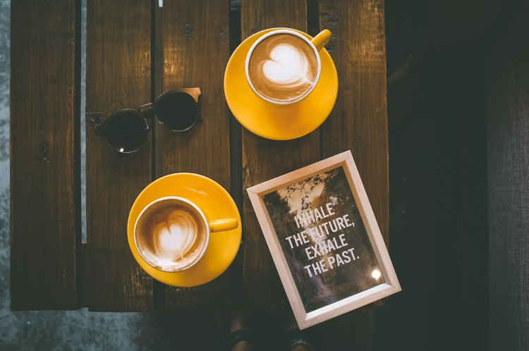 Inspiring coffee and sign reading inhale the future, exhale the past