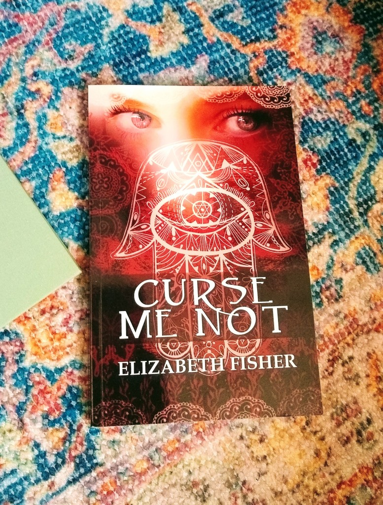 "Closeup of Elizabeth Fisher's ""Curse Me Not,"" with a woman's eyes gazing out over mystical symbols on the cover."